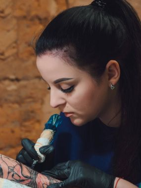 Portrait of brunette female tattooer in violet clothing making tattoo on the mans arm of her client with gun in studio. Young business woman in workshop.