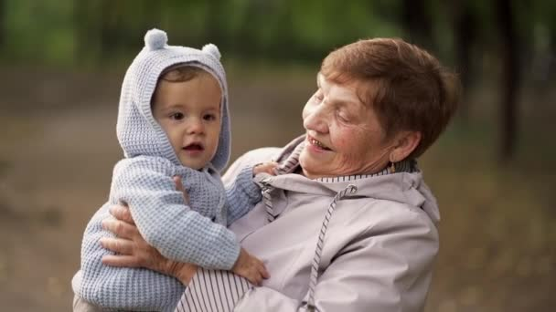 Grandmother with baby boy in autumn park having fun, smiling, playing. Grandson is happy to communicate with elderly great-grandmother