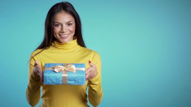 Hezká brunetka dá dárek a podá ho kameře. Je šťastná, usmívá se. Dívka na modrém pozadí. Pozitivní vánoční záběry