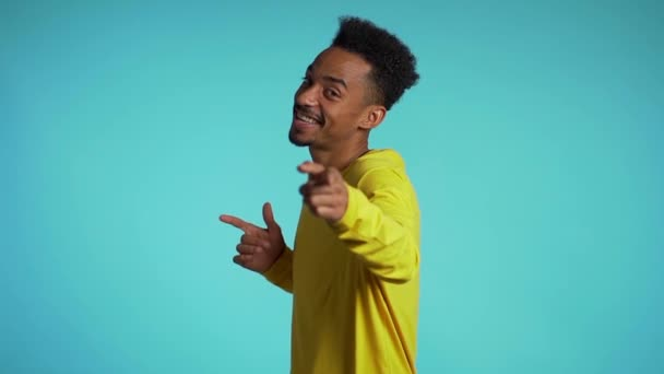Young african american man smiling and dancing in good mood on blue background.Unstoppable fun, happiness, comical portrait of guy isolated.