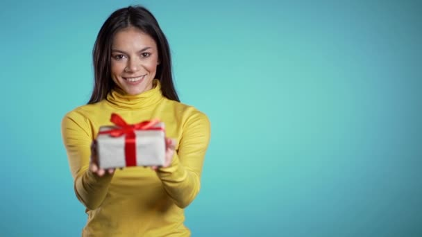 Míchaná závodnice dá dárek a podá ho kameře. Je šťastná, usmívá se. Dívka na modrém pozadí. Pozitivní vánoční záběry
