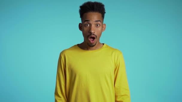erstaunt Mixed Race Mann schockiert und sagte wow. schöner afrikanisch-amerikanischer Kerl mit Afro-Haaren überrascht vor der Kamera über blauem Hintergrund.
