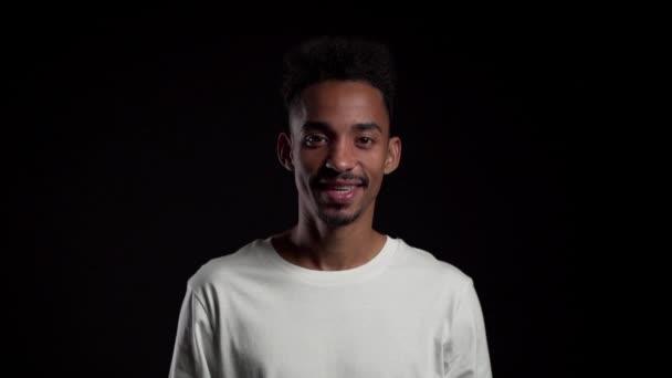 Mladý africký Američan v bílém na černém pozadí studia ukazuje ano znamení po hlavě. Pozitivní záběry, emoce, pojetí řeči těla.