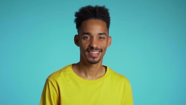 Jóképű afro-amerikai férfi divatos göndör frizurával, kék stúdió háttérrel. Vidám fickó mosolyog és a kamerába néz..