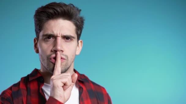 Evropan pohledný muž drží prst na rtech přes modré pozadí. Gesto shhh, tajemství, ticho. Kopírovat prostor.
