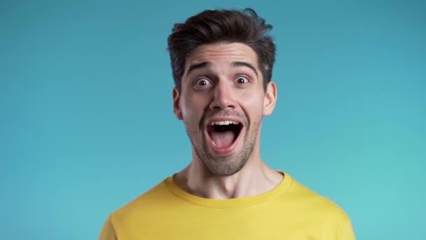 Překvapený Evropan šokovaný, když řekl Wow. Fešák chlap se stylovým účesem překvapen kamerou přes modré pozadí.