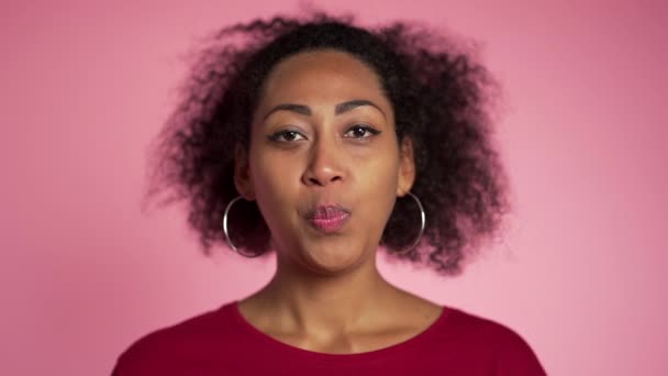 Playful girl in red wear blows bubblegum, chewing gum in slow motion. Pretty african american woman stands on pink background.
