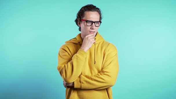 Thinking man looking up and around on blue background. Worried contemplative face expressions. Handsome male model in yellow hoodie.