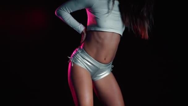 Szexi nő rövid ezüst rövidnadrágban táncol modern tánc - twerk. Lány remeg, remeg a feneke közelről fekete háttér, neon fény.