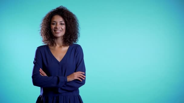 Attractive african american woman with afro hair in business clothing smiling to camera over blue wall background. Copy space. Cute mixed race girls portrait