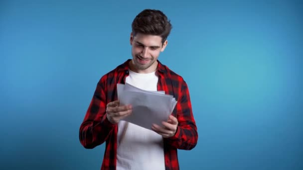 Young handsome man checks documents, utility bills, report. Businessman isolated on blue background. He is satisfied with work of corporate staff.