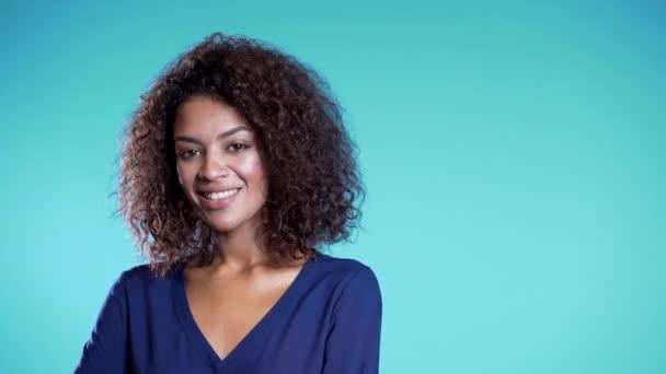 Atraktivní africká americká žena s afro vlasy v obchodním oblečení s úsměvem na kameru přes modrou zeď pozadí. Rozumím. Roztomilé smíšené rasy dívky portrét