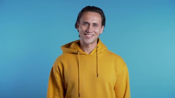Fešák evropský muž s módním účesem ve žlutém oblečení na modrém pozadí studia. Veselý chlapík se usmívá a dívá se do kamery. 4k