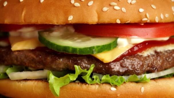 Čerstvé mňam grilovaný burger rotující na hranolky a černý kouř pozadí.