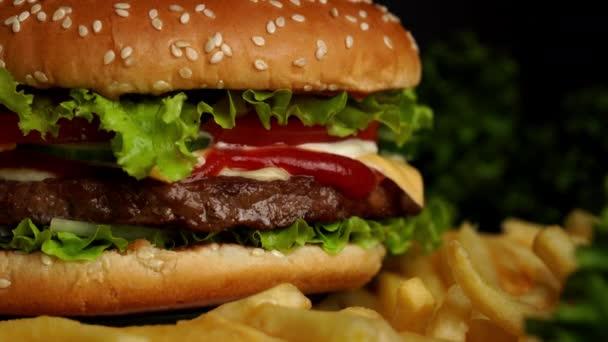 leckeres Fast-Food-Konzept. frisch gegrillter Burger vom Grill mit Fleischpatty, Tomaten, Gurken, Salat, Zwiebeln und Sesam. ungesunder Lebensstil. Lebensmittel-Hintergrund. 4k