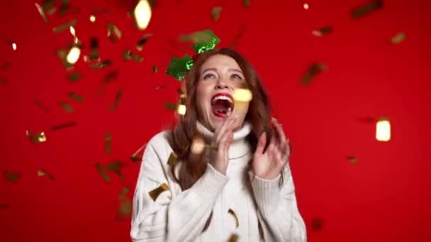 Izgatott nő fagyöngy fejkoszorúban táncol, tapsol, szórakozik, örül a konfetti esőnek a vörös stúdióban. Fogalom karácsony, újév, boldogság, party, győzelem.