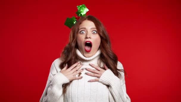 Portrét roztomilé dívky ve vánočním vějíři šokován, říká Wow. Hezká žena se usmívá, skákání, příjemně překvapen kamerou přes červené pozadí.
