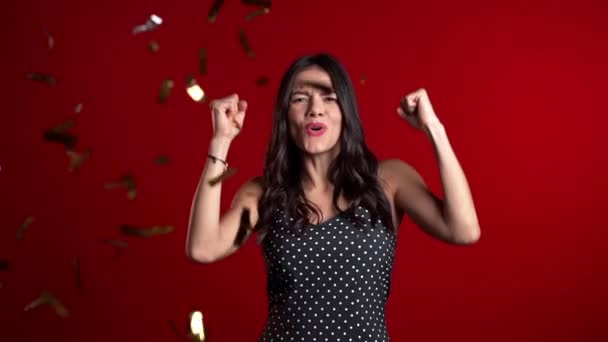 Excited woman showing yes yeah gesture, dancing, having fun, rejoices over confetti rain in red studio. Concept of Christmas, New Year, happiness, party, winning