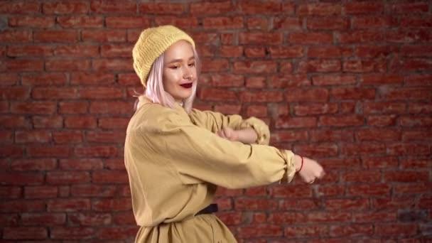 ungewöhnliche Frau mit rosa Haaren, die Spaß hat, lächelt, im Studio vor Backsteinhintergrund tanzt. Musik, Tanzkonzept, Zeitlupe