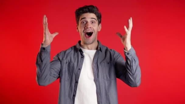 Ano, vítězný gesto. Šťastný Evropan se raduje. Fešák chlap se stylovým účesem překvapen kamerou přes červené pozadí