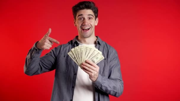 Man in denim shirt with surprised happy face holding US currency. Person with money. New dollars in hands on red studio background .