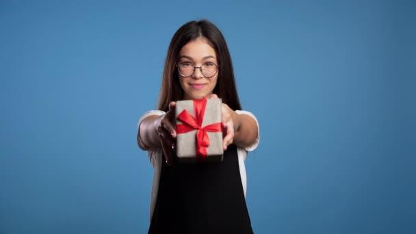 Csinos barna ázsiai lány szemüvegben ajándékot ad, és odaadja a kamerának. Boldog, mosolyog. Kék hátterű lány. Pozitív ünnepi felvétel