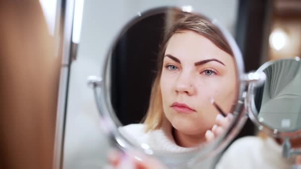 Pretty woman making make-up with shadow palette in front of mirror at home. Beauty, cosmetics, artist concept.