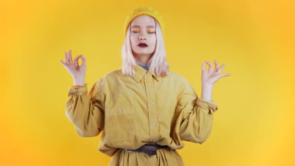 Positive girl relaxing, meditating. Woman calms down, breathes deeply with mudra om on yellow studio background. Young unusual woman portrait.