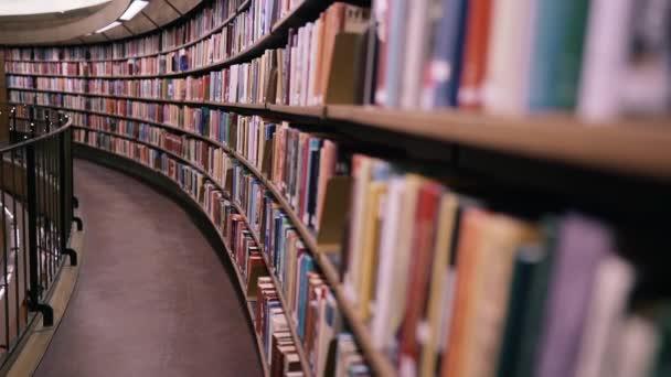 Stedicam zastřelen. Kamera se pohybuje podél polic naplněných papírovými knihami. Obrovská kulatá knihovna ve Stockholmu, Švédsko