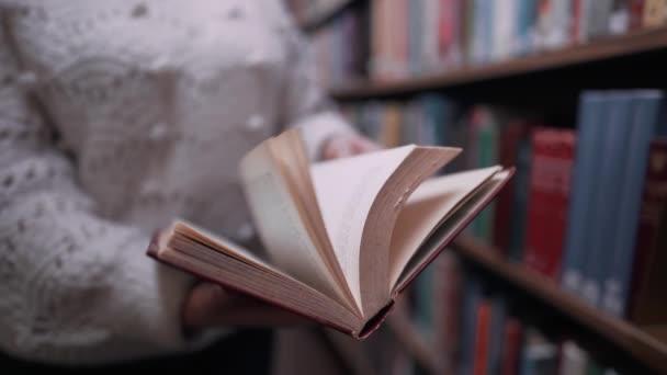 Nerozpoznatelná žena krásně obrací stránky staré papírové knihy ve velké knihovně na policích. Krásná scéna. Vzdělání, věda, univerzitní koncept.
