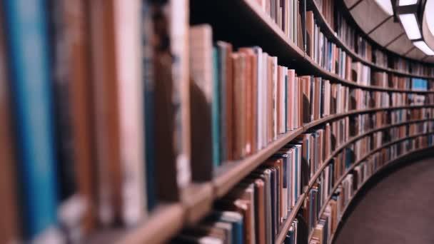Stehaufmännchen erschossen. Die Kamera bewegt sich an Regalen entlang, die mit Papierbüchern gefüllt sind. Die riesige runde Bibliothek in Stockholm, Schweden