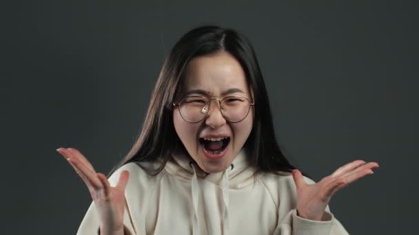 Junge verängstigte schreiende asiatische Mädchen schockiert isoliert vor grauem Hintergrund. Gestresste und depressive Koreanerin wegen schlechter Nachrichten