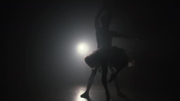 Profi balett pár táncol reflektorfényben füst a nagy színpadon. Gyönyörű fiatal nő és férfi reflektorfényben háttér. Érzelmi duett, koreografikus művészet. Lassú mozgás. 4k