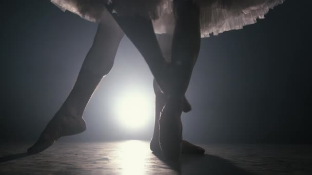 Close up of ballet couple of dancers as they practices exercises on dark stage or studio. Womans and mans feet in pointe shoes. Ballerina shows classic ballet pas. Slow motion. Flare shot.