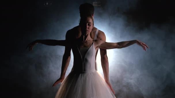 Kecses balerina és férfi partnere táncoló elemei klasszikus vagy modern balett sötétben reflektorfényben. Egy pár füstöl fekete háttérrel. Művészeti koncepció.