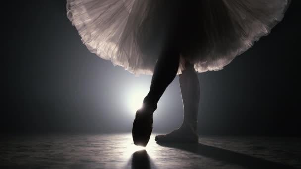 Großaufnahme einer Balletttänzerin, die auf dunkler Bühne oder im Studio Übungen macht. Frauenfüße in Spitzenschuhen. Ballerina zeigt klassischen Ballett-Pas. Zeitlupe. Schlagschuss.
