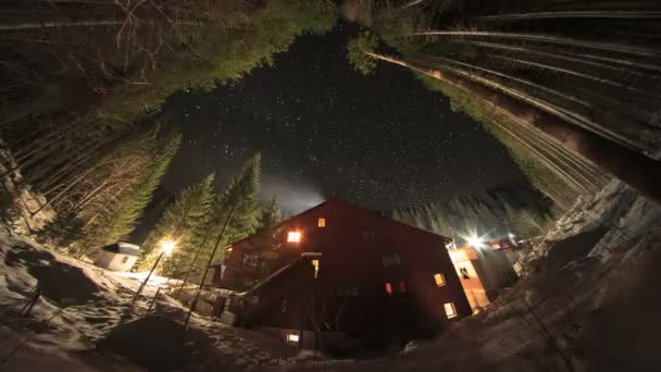 4K Time Lapse. Starry sky and a house in the mountains among the trees.