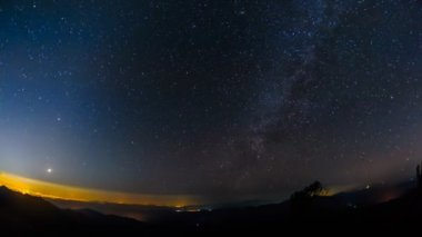 Milky way and star time-lapse moving across the sky with silhouetted on the hight mountain in forest, Thailand.