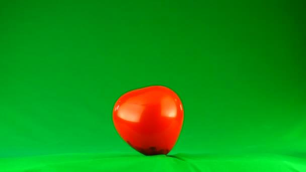 Zeitlupenexplosion eines roten Ballons auf grünem Hintergrund