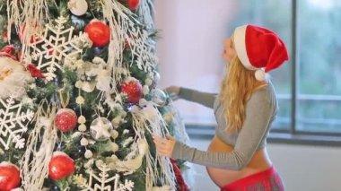 Pregnant woman near Christmas tree. Full HD Video