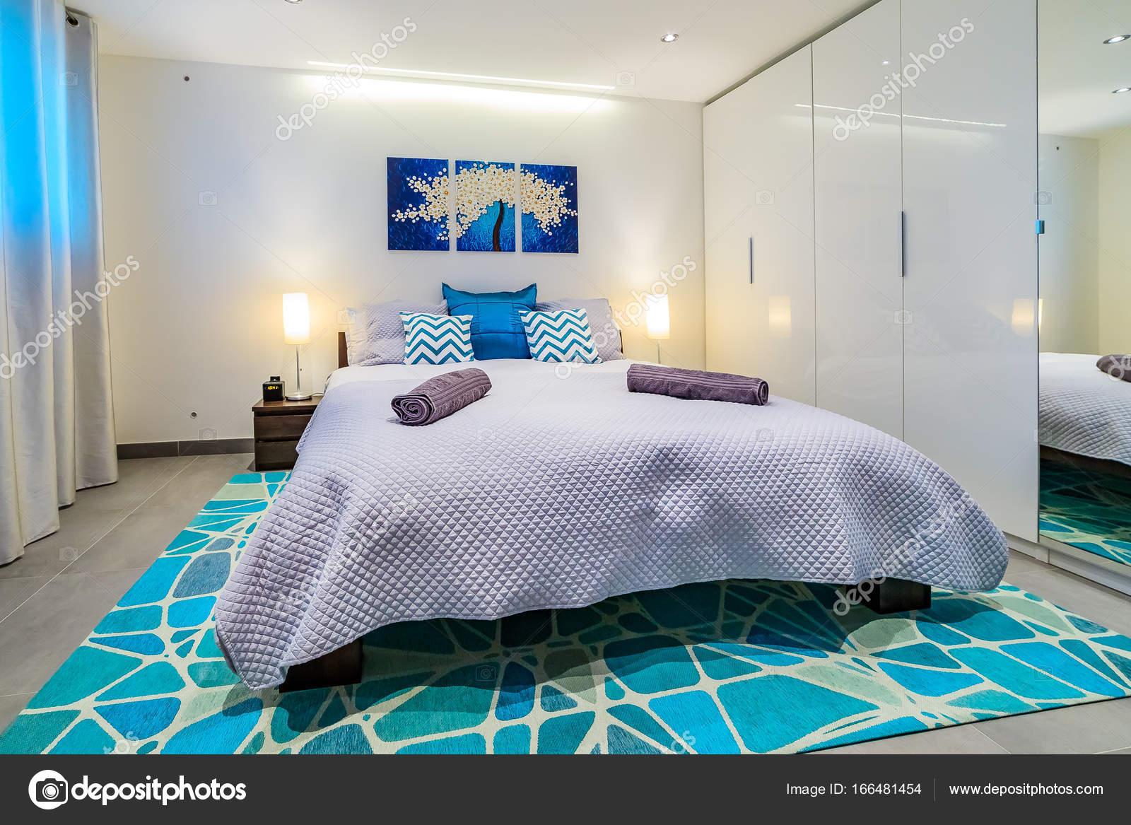 Großes Bett Mit Hotelbetreibern Und Leuchtend Blauen Kissen In Einem  Modernen Schlafzimmer, Wandkunst Malerei Und Lichter U2014 Foto Von SvetlanaSF