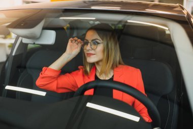 young woman looking in the rearview mirror of a car