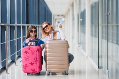 Mother and little daughter with luggage at airport terminal ready for vacation.