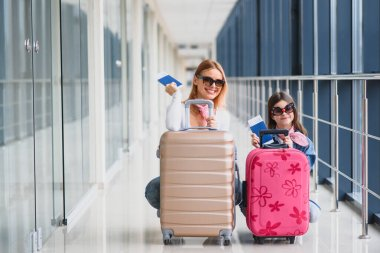 Mother and little daughter with luggage and boarding pass and passport at airport terminal ready for vacation. High season and vacation concept. Relax and lifestyles