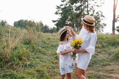 Stylish mother and handsome daughter having fun on the nature. Happy family concept. Beauty nature scene with family outdoor lifestyle. family resting together. Happiness in family life. Mothers day