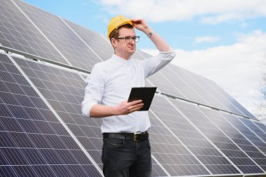 solar panels and blue sky.Man standing near solar panels. Solar panel produces green, environmentally friendly energy from the sun.