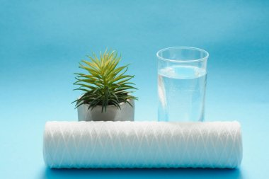 Glasses of dirty and clear water and filter cartridges to domestic water treatment systems at bright blue background. Concept of water treatment.