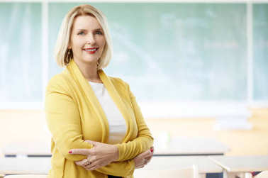 Lovely mature female teacher standing with arms crossed in front of chalkboard in classroom.