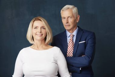 Studio portrait of senior business people standing at dark background. Beautiful mature woman wearing shirt and senior man wearing suit while standing behind her.