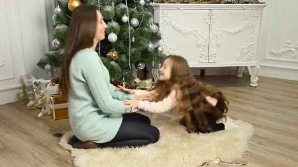 Mutter und Tochter spielen neben dem Weihnachtsbaum